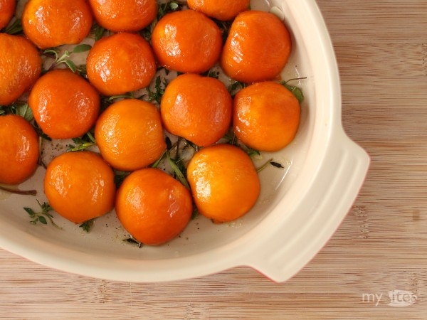 Halved and Peeled Apricots Arranged on a Bed of Herbs